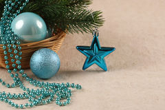 Christmas tree ornaments balls, beads and spruce branch in a bas. Ket on a cloth background Royalty Free Stock Image