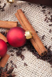 Christmas tree ornaments and cinnamon sticks Royalty Free Stock Photos