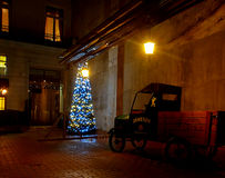 Christmas tree with outbuildings. Illuminated Christmas tree and an old car in the annexe on Piotrkowska Street in Lodz Stock Photography