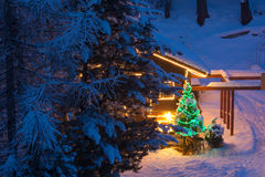 Christmas tree outdoor decoration. In a snowy night with gifts and illuminatedn wooden  home Stock Photo