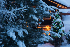 Christmas tree outdoor decoration. In a snowy night with gifts and illuminatedn wooden  home Royalty Free Stock Photo