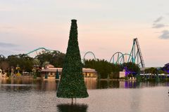 Christmas Tree over the lake and colorful rollercoaster on sunset background in International Drive area. Orlando, Florida; November 24, 2018. Christmas Tree stock photo