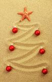 Christmas tree on painting in sand with red starfish and red matt christmas balls Royalty Free Stock Image