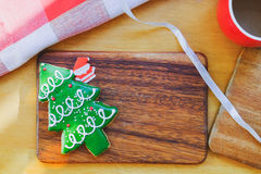 Christmas tree and paper Santa on wooden plate. Christmas tree cookie and paper Santa on wooden plate. Christmas theme table Stock Photography