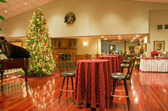 Christmas tree and party area. A view across a highly polished hardwood floor to a Christmas tree and a set of high tables and chairs prepared for a holiday stock images