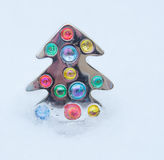 Christmas Tree Pin. Small Christmas tree pin placed in the snow Royalty Free Stock Photos