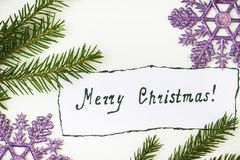 Christmas tree with pine cones and a congratulatory inscription. On the paper on a white the background is decorated with a snowflake Stock Photos