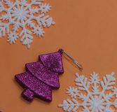 Christmas tree pink, decorative element with white snowflakes two lies on the orange surface stock images