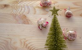 Christmas tree decorated with roses. Christmas tree with pink roses on wooden planks and space for text Stock Image