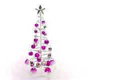 Christmas tree of pink and silver jingle bells. Christmas tree made out of pink and silver jingle bells on pink shimmery fabric Stock Image