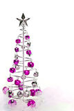 Christmas tree of pink and silver jingle bells. Christmas tree made out of pink and silver jingle bells on pink shimmery fabric Stock Photography