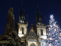 Christmas tree in Prague. Statue silhouette of Jan Hus and St. Teyn gothic cathedral with lighting christmas tree on Old Town Square in Prague Royalty Free Stock Images
