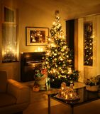 Christmas tree with present sack. Christmas tree with burlap sack full of gift boxes in living room warm feeling stock images