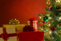 Christmas tree with presents. Against red background stock photos