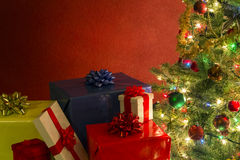 Christmas tree with presents. Against red background stock image