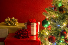 Christmas tree with presents. Against red background royalty free stock images
