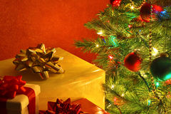 Christmas tree with presents. Against red background royalty free stock photo