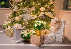 Christmas tree with presents. Decorated Christmas tree with wrapped presents on the bottom of the tree stock photo