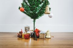 Christmas tree with Christmas presents and decorations on wooden floor, in living room. Christmas tree with Christmas presents and decoration on wooden floor, in Stock Images