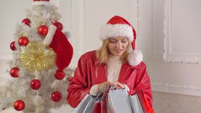 Christmas tree, presents and gift boxes under it. New Year decorations. New year woman. Young lady gifts by the stock video footage