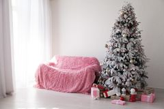 Christmas tree with presents new year`s White room sofa. Christmas tree with presents new year`s White room royalty free stock image