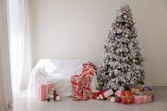 Christmas tree with presents new year`s White room sofa. Christmas tree with presents new year`s White room stock photo