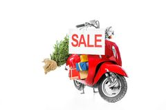 Christmas tree and presents on red scooter with sale sign,. Isolated on white royalty free stock images