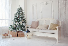 Christmas tree with presents underneath in living room. Vintage christmas tree with presents underneath in living room Royalty Free Stock Images