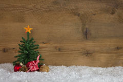 Christmas tree with presents on a wooden background with snow. stock images