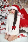 Christmas tree. Pretty teen girl in santa hat and white knitted Royalty Free Stock Photos