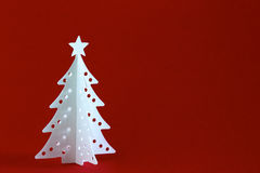 Christmas tree on red. White Christmas tree isolated on red background with space for text Royalty Free Stock Images