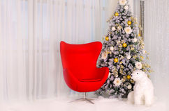 Christmas tree with red armchair and a polar bear in the interior. Beautiful Christmas Background Stock Images
