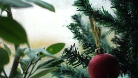 Christmas tree with a red ball and rain outside the window. The focus shifts from the foreground, leaves, to the back.  stock footage