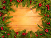 Christmas tree and red berries frame on the wooden background wi Stock Photos