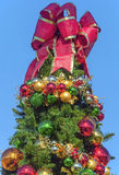 Christmas Tree. A red bow sits on top of an outdoor Christmas Tree Stock Photos