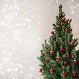 Christmas tree with red Christmas decorations on holiday background with snow, blurred, sparking. Glowing. Happy New Year and Xmas theme royalty free stock photo