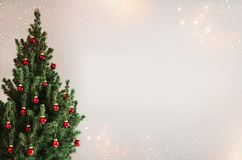 Christmas tree with red Christmas decorations on holiday background with snow, blurred, sparking. Glowing. Happy New Year and Xmas theme stock image