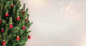 Christmas tree with red Christmas decorations on holiday background with snow, blurred, sparking. Glowing. Happy New Year and Xmas theme stock photos