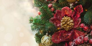 Christmas tree with red design flowers and holly berries as decor with copy space on blurred bokeh background in mall. Close up. Royalty Free Stock Photo
