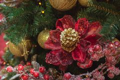Christmas tree with red design flowers and holly berries as decor with copy space on blurred bokeh background in mall. Close up. Royalty Free Stock Image