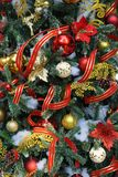 Christmas tree with red, gold and white ornaments and red ribbon garlands Royalty Free Stock Image