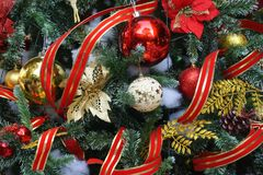 Christmas tree with red, gold and white ornaments and red ribbon garlands Stock Photography