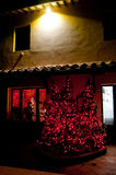 Christmas tree with red lights at Tuscan farm. Tuscan Farmhouse with tree decorated with lights and red stars Royalty Free Stock Photography