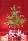 Christmas tree, red presents. Miniature Christmas tree with miniature red ornaments, red presents and elegant red Stock Photography