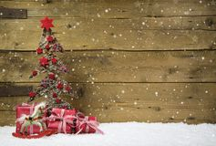 Christmas tree with red presents and snow on wooden snowy background.
