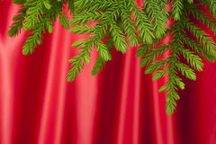 Christmas Tree Red Satin Background. A Christmas tree branch with a red satin material background Royalty Free Stock Photo