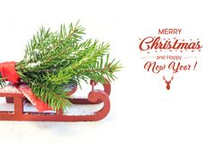 Christmas tree on red sled on a white background. Copy space. Holyday card. Close up. Holiday cheers Stock Images