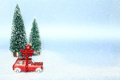 Christmas tree on red toy car. Snowy and light blue background. Holiday, Christmas, xmas concept. Space for text royalty free stock image