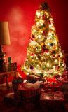Christmas tree on red wall. Nicely decorated Christmas tree with lights with dark red wall as background stock photo