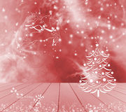 Christmas tree, reindeer and snow on red background. Red empty wooden table ready for your product display montage. Happy holidays Royalty Free Stock Images
